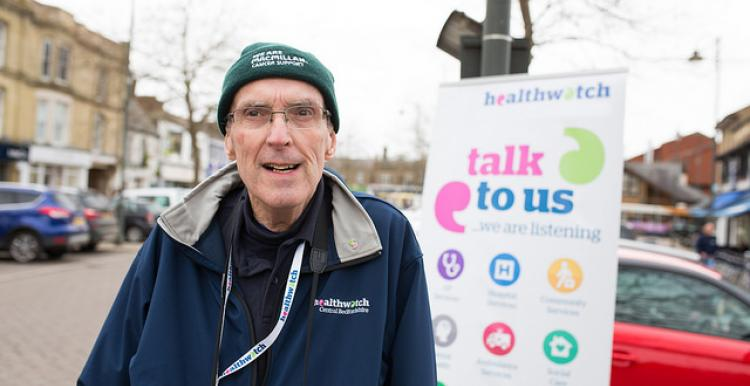 Older volunteer standing infront of a Healthwatch banner at an event