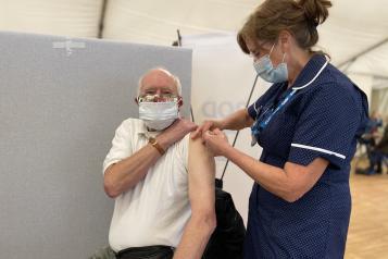 Nurse giving Covid vaccine to man