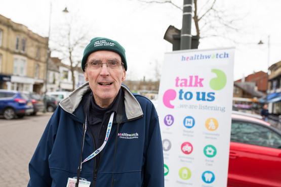 Man standing infront of Healthwatch banner