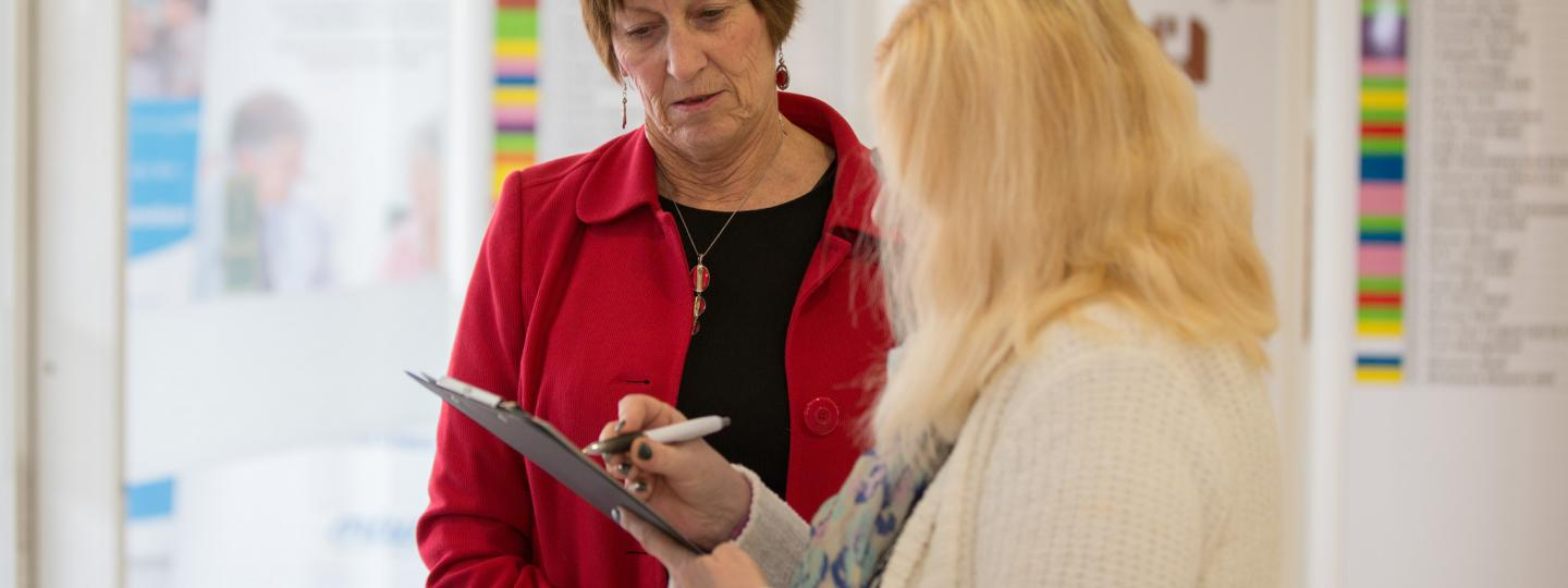 volunteer with clipboard talking to woman
